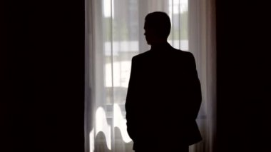 Silhouette of stylish man in suit looking out the window — Stock Video