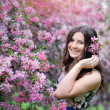 Beautiful girl in spring park with flowers lifestyle portrait, happy woman with blooming cherry tree. Skin care and beauty. Smiling teen girl in spring garden enjoying nature. Spring concept. Series. — Stock Photo #45789121