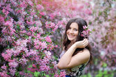 Beautiful girl in spring park with flowers lifestyle portrait, happy woman with blooming cherry tree. Skin care and beauty. Smiling teen girl in spring garden enjoying nature. Spring concept. Series. — Stock Photo