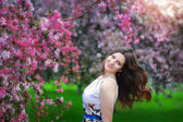 Beautiful young girl in spring flowers garden lifestyle portrait — Stock Photo