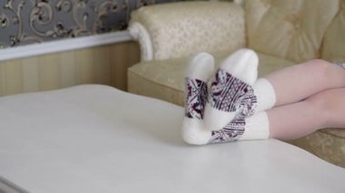 Female legs in beautiful knit socks on the table — Stock Video