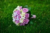 Beautiful wedding bouquet t lie on the grass — Stock Photo