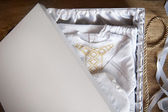 White robe embroidered with gold in a box — Stock Photo