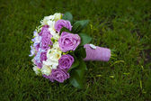 Wedding bouquet of purple and white roses lying on grass — Stock Photo