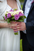 Beautiful wedding bouquet in brides and grooms hands — Stock Photo