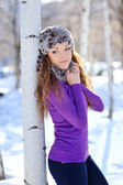 Beautiful girl stands near the birch in winter — Foto Stock