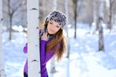 Beautiful girl standing near birch tree in winter park — Stock Photo