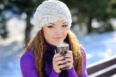 Beautiful girl sitting on a bench with a cup of coffee. Winter — Stock Photo