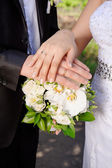 Hand the bride and groom with rings on wedding bouquet — Stock fotografie