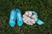 Bridal bouquet and turquoise shoes on green grass — Stock Photo