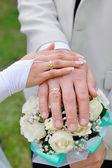 Handen met trouwringen en bruiloft boeket — Stockfoto