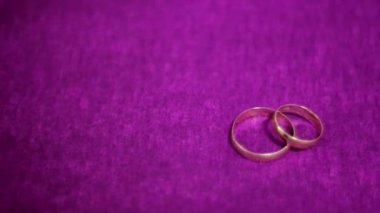 Two beautiful wedding ring on a dark purple background — Stock Video
