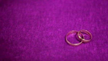 Twee mooie trouwring op een donkere paarse achtergrond. — Stockvideo