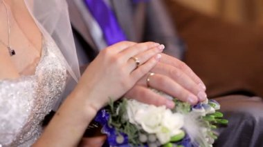 Hands of the bride and groom are on the wedding bouquet — Stock Video