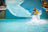 Beautiful girl pulls off the slides at the water park — Stock Photo