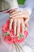 Hand the bride and groom with the rings lying on the bridal bouquet — Stock Photo