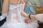 Bridesmaid helping the bride lacing up her dress closeup portrait — Stock Photo