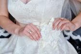 Bride adjusts white bow on her dress — Stok fotoğraf