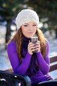 Beautiful girl sitting on a bench in the park with a cup of winter — Stock Photo