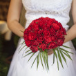 Wedding bouquet of red roses and leaves in brides hands — Stock Photo #49583779