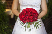 Wedding bouquet of red roses and leaves in brides hands — Stock Photo