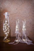 Decorated wedding glasses and bottle of champagne — ストック写真