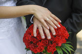 Hands and rings bride and groom on wedding bouquet — Stock Photo