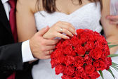 Hands of bride and groom with rings on wedding bouquet — Stock Photo