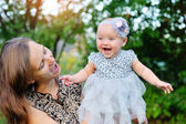 Happy mother and daughter smiling outdoors in a park — Stock Photo