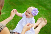 Beautiful happy little baby girl sitting on a green meadow  dand — Stock Photo
