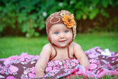 A cute little baby is looking into the camera and is wearing a b — Stock Photo