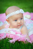 Portrait of little cute baby girl lying in the park and a bandag — Stock Photo