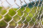 Wire fence with futsal field on background — Stock Photo
