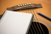 Notebook and pencil on guitar — Stock Photo