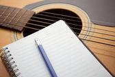 Taccuino e matita su chitarra — Foto Stock