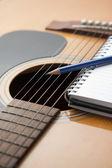 Cuaderno y un lápiz en la guitarra — Foto de Stock