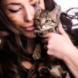 Young woman holding kitten - Stock Photo