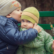 Stock Photo: Brother kissing little sister, sitting on bench