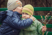 Brother kissing little sister, sitting on a bench — Stock Photo