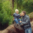 Father and son in bamboo grove near huge tree — Stock Photo #23062706