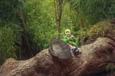 A little girl sitting on the big tree — Stock Photo
