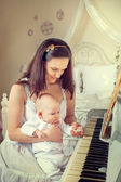 A mother with a newborn around the piano — Stock Photo