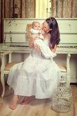 Eine mutter mit einem neugeborenen baby auf dem hintergrund-klavier — Stockfoto