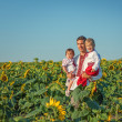 A father and two children in Ukrainian costume at sunset in a fi — Stock Photo