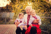 Grandparents with grandchildren in Ukrainian costume at sunset — Stock Photo