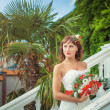 A beautiful bride in nature with a bouquet of red — Foto de Stock