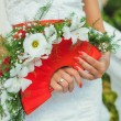 Bride holding beautiful red wedding flowers bouquet — Stock Photo #23360226