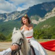 Bride on a horse looks at the groom - Stock Photo