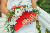 Bride holding beautiful red wedding flowers bouquet — Stock Photo