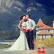 Bride and groom kissing on the background of mountains — Foto Stock